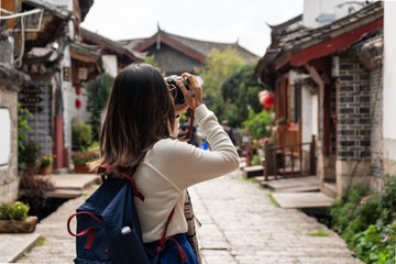 Young woman traveler walking and photographing at lijiang old town in Yunnan province, China