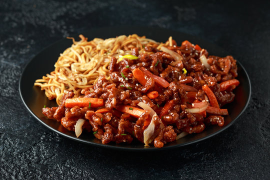 egg noodles with bean sprouts and Crispy shredded beef on black plate