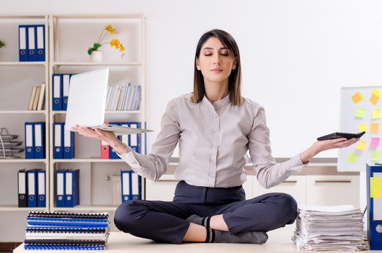 Young female employee doing exercises at workplace