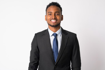 Happy young handsome African businessman in suit smiling
