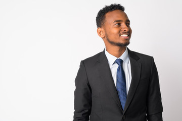 Portrait of happy young handsome African businessman thinking