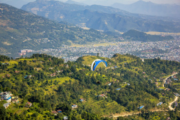paraglider on a blue parachute flies in a green mountain valley with the city of Pokhara