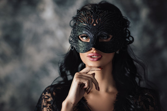 portrait of sexy beautiful woman in lace black erotic lingerie and carnival mask on dark background