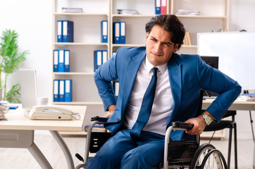 Male employee in wheelchair working at the office