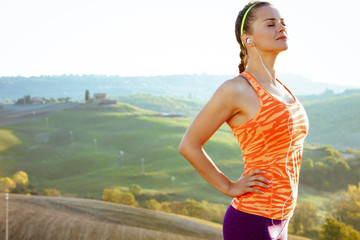 sports woman in front of scenery of Tuscany listening to music