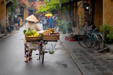 Woman walking in Hoi An with fruits