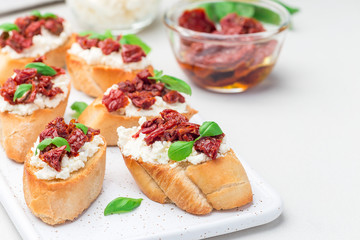 Bruschetta with sun dried tomato, feta and philadelphia cheese and basil on ceramic plate, horizontal, copy space