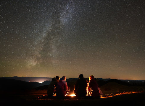 Night summer camping in the mountains. Back view group of four friends tourists sitting on a bench made of logs together around campfire under amazing night starry sky full of stars and Milky way.