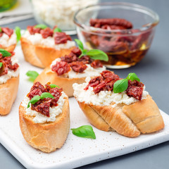 Bruschetta with sun dried tomato, feta and philadelphia cheese and basil on ceramic plate, square format