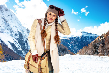 solo traveller woman in front of mountain landscape with bag