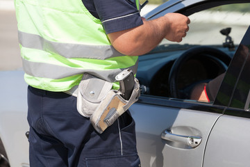 Police officer checking driving license of a car driver during traffic control