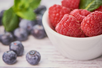 macro photo of raspberries in a bowl beside are lying some blueberries on white wooden surface
