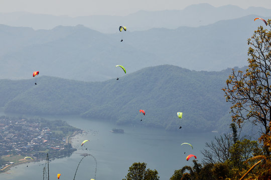 Flying on a paraglider. Beautiful view with mountains and colorful paragliders. Extreme vacation travel