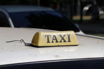 Taxi light sign or cab sign in drab brown color with black text on the car roof at the street blurred background