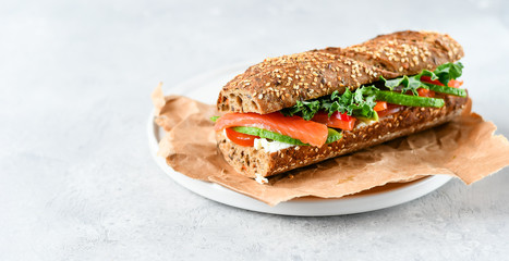 Canvas Prints Snack sandwich from a cereal baguette with avocado, salmon, cream cheese, tomatoes and lettuce leaves on a white plate. light background, selective focus and copy space