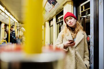 junge Frau, Mädchen, Teenager, mit Smartphone, fährt mit der U-Bahn