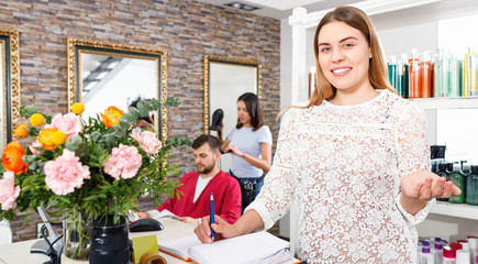 Portrait of young woman  administrator inviting to beauty salon