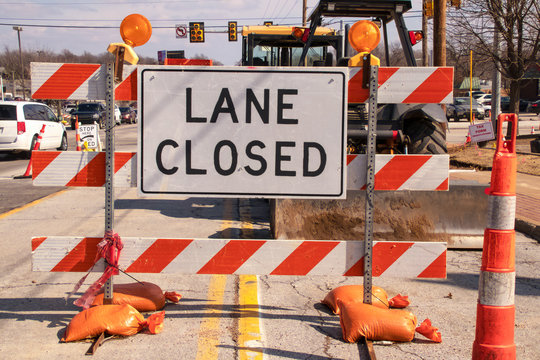 Lane Closed sign at messy construction urban intersection with sand bags traffic cones heavy equipment working and cars stopped at stoplight