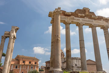 Pillars and ruins of the ancient Saturn Temple in Forum Romanum. Ruins of pillars of Temple of Vespasian are in the background. Rome. Italy.