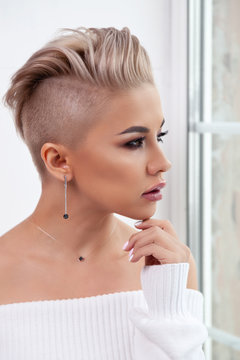 Closeup sexy blonde model with bright make-up, bare shoulders and short hair with shaved temples in modern round silver jewelry earrings and necklace. Сoncept shooting for bijouterie store