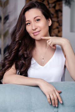 Closeup cute beautiful brunette girl with long hair in silver jewelry earrings and necklace. Сoncept of gentle, elegant, delicate, romantic jewelry, bijouterie on the model