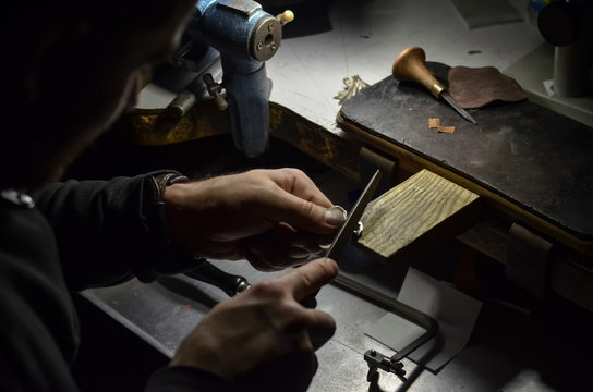 The master jeweler holds the working tool in his hands and makes jewelery at his workplace in the jewelry workshop.