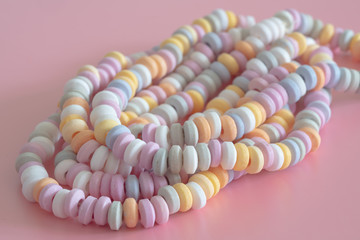 sweets Beads and bracelets candy on a pink background