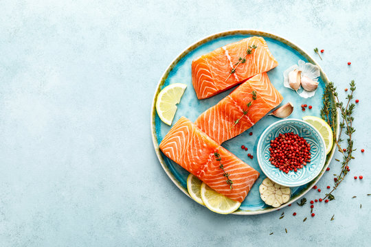 Seafood. Fresh raw salmon or trout fillets with ingredients, top view, space for a text
