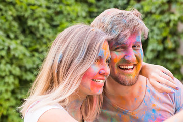 Festival of holi and technology concept - young couple making selfie at the festival