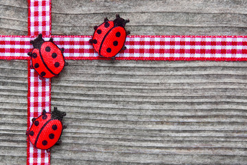 Decoration with ladybirds and ribbon against wooden background