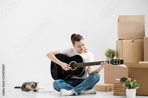 A Young Woman In White T Shirt Is Resting And Playing The Guitar On Background Of Cardboard Boxes New Empty Apartment With Little Pet Cat