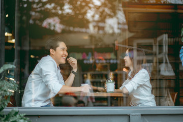 Asian couple talking happily in the cafe during the daytime.