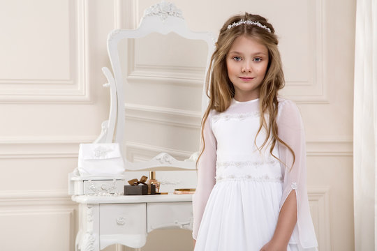 Portrait of cute little girl on white dress and wreath on first holy communion background church gate - Image. Young  model in the white communion dress stands in an elegant palace