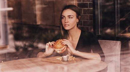Young woman sitting and eating an hamburger through the window