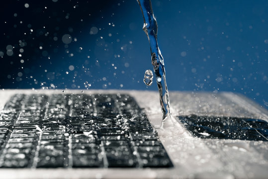 A stream of water pours on the laptop keyboard.