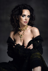 Young sensual beautiful sexy woman posing in spring fashion body jacket and expensive jewelry naked on dark