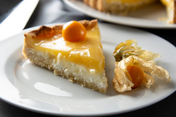 Lemon curd pie. Piece, slice of homemade delicious pie ,tart filled with lemon curd. Sweet dessert. Lemon curd pie decorated with physalis.