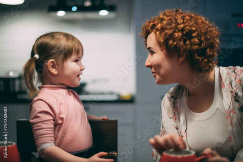 Mom and daughter have dinner in the evening at home in the