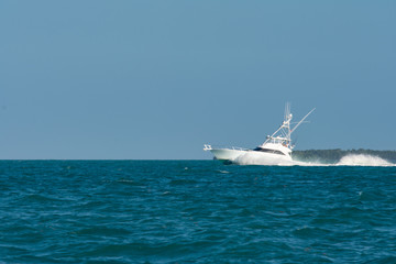 White luxury yacht sport fisher with breaking bow wave.
