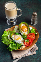 Avocado baked with egg on wooden plate with