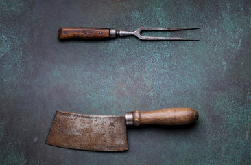 Vintage meat cleaver and fork on dark background with copy space