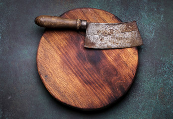 Meat cleaver on round cutting board on grunge dark background. Top view with copy space.