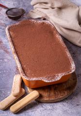 Italian tiramisu dessert cake in dish with cocoa powder on blue background