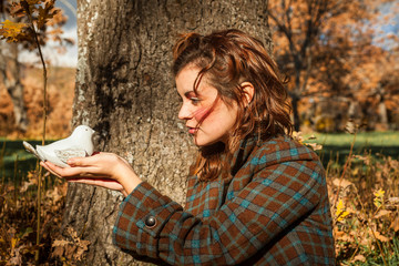 Close up portrait of a woman holding a bird of stone. Concept. Love. Woods