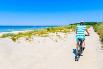 Fototapete - Young woman riding bicycle along sandy beach on Hiddensee island, Germany, Baltic Sea