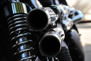 close up rear view of a powerful classic black vintage motorcycle showing suspension and shiny chrome exhaust pipes