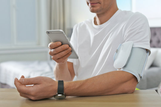 Man checking blood pressure with modern monitor and smartphone at table indoors, closeup. Cardiology concept