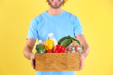 Delivery man holding wooden crate with food products on color background, closeup