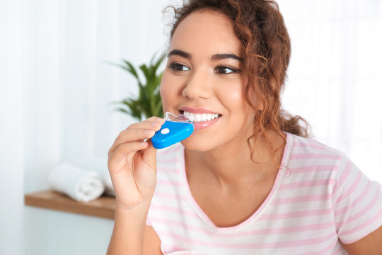 Young African-American woman using teeth whitening device at home