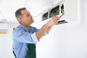 Electrician with screwdriver repairing air conditioner indoors Fototapete
